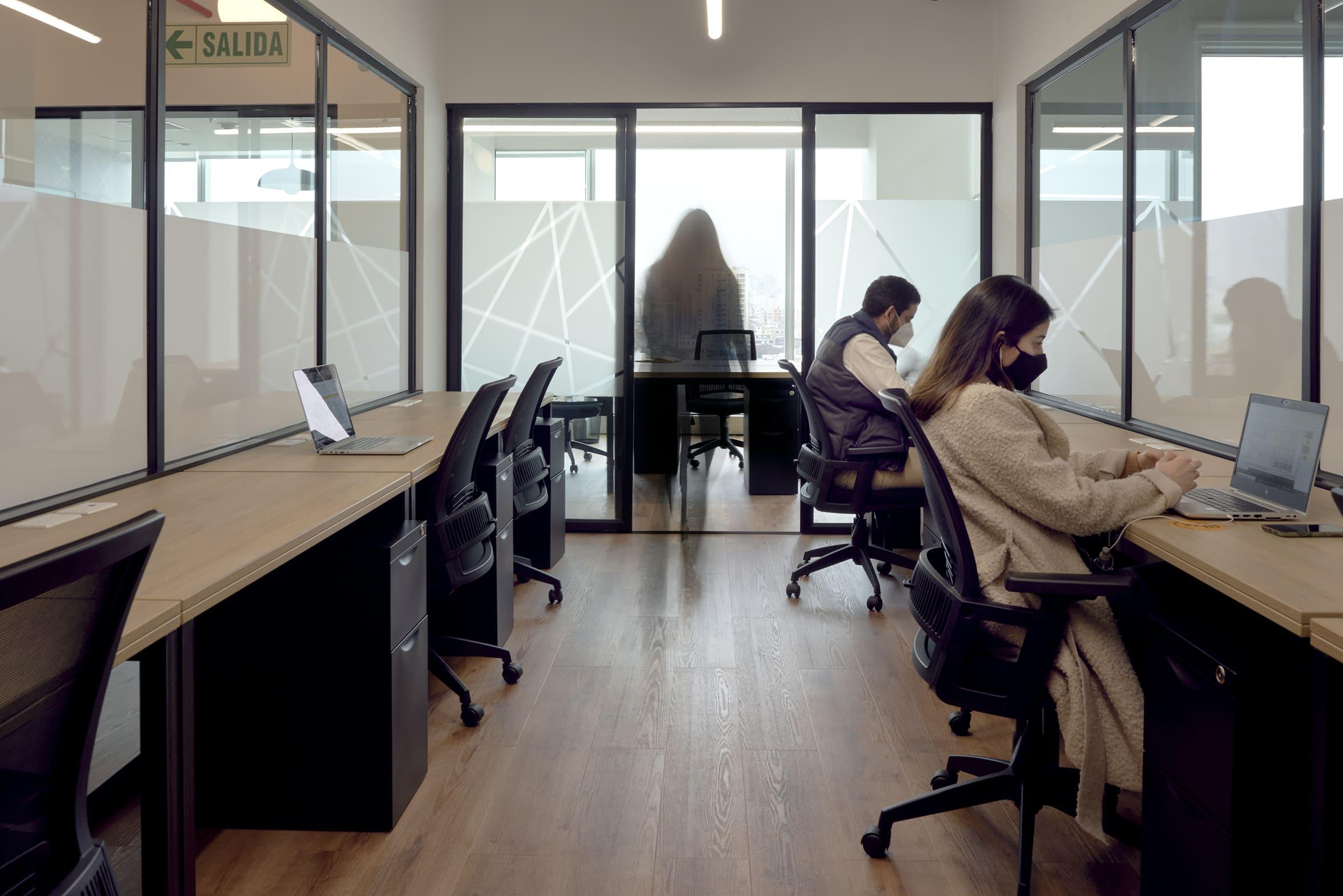 empleados trabajando con mascarilla en la oficina