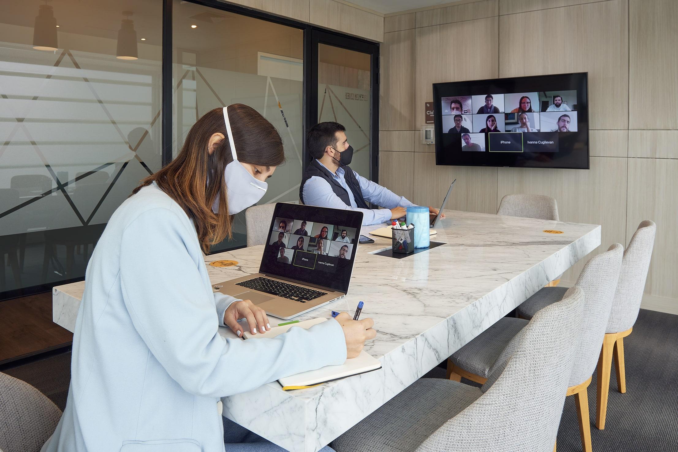 colaboradores realizando una presentacion virtual en una oficinas satelite