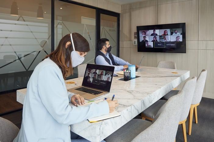 dos colaboradores reunidos en una oficina y presentando un proyecto al equipo en videollamada
