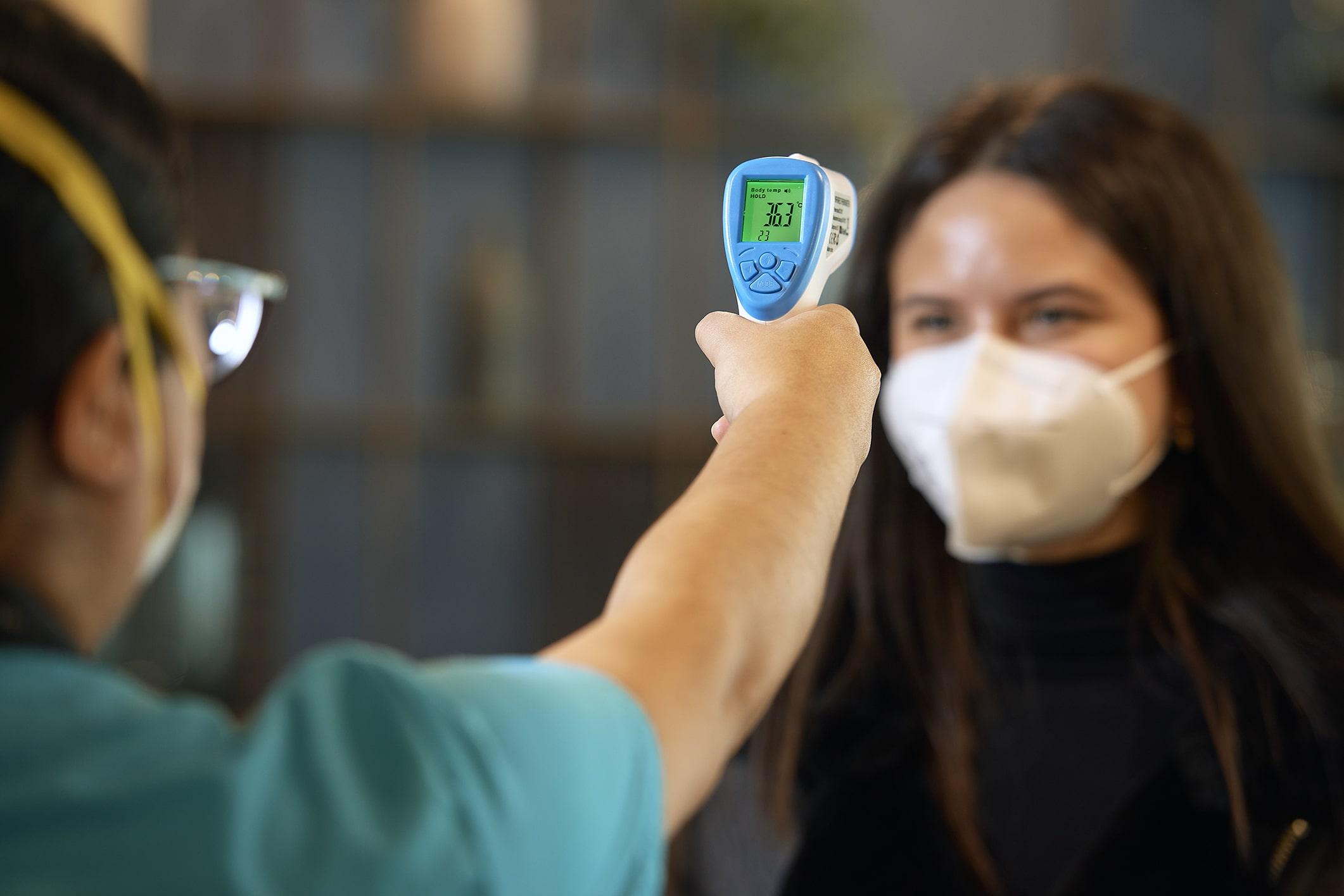 enfermera tomando la temperatura de una trabajadora