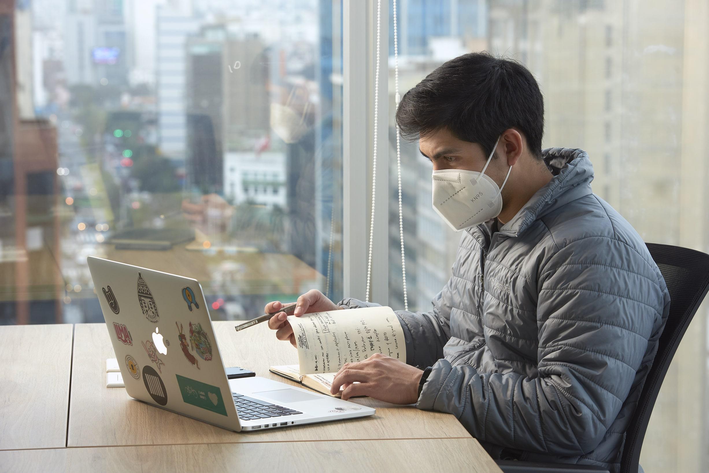 hombre joven trabajando en su laptop y revisando documentos