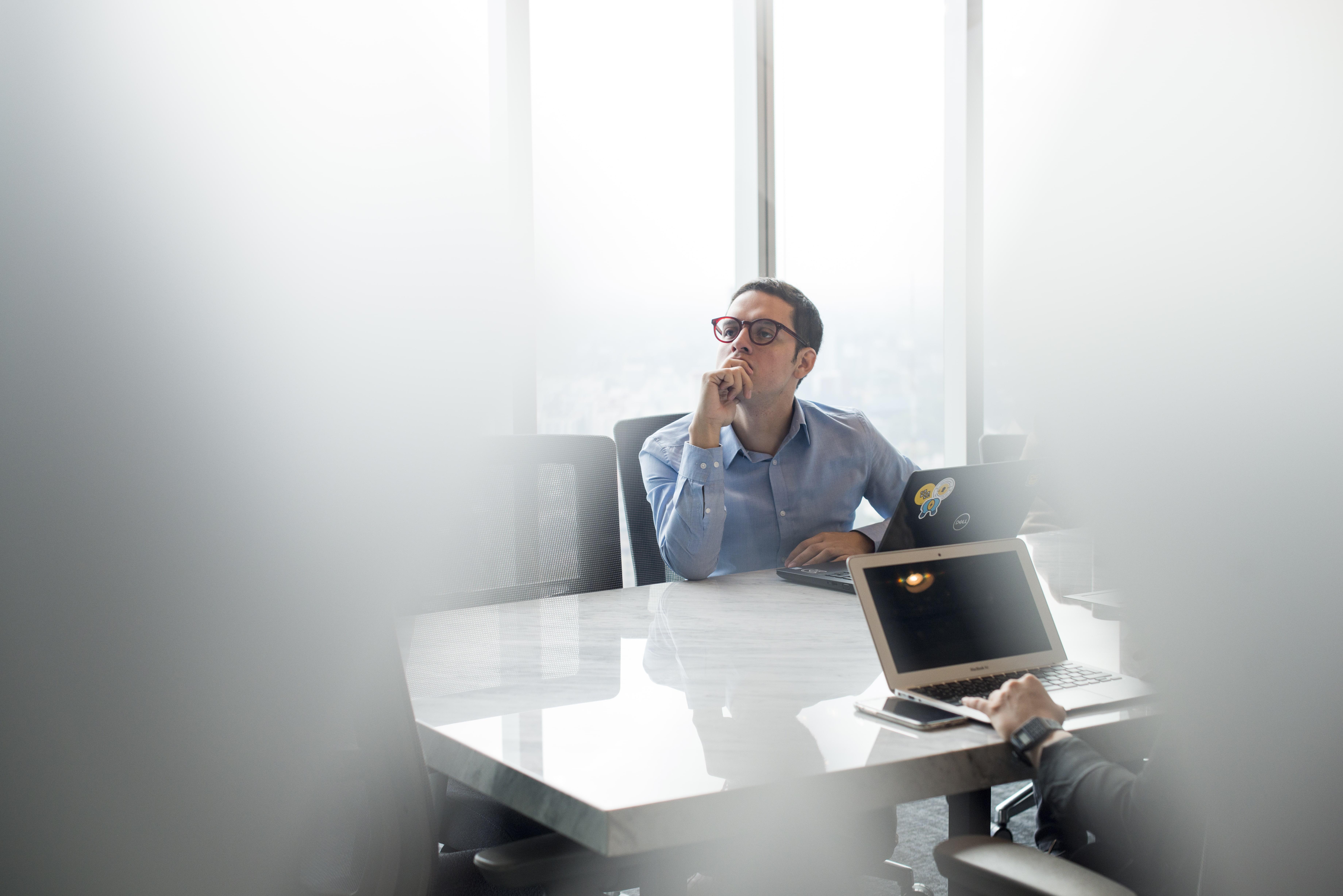 hombre reflexionando en una sala de reuniones de comunal