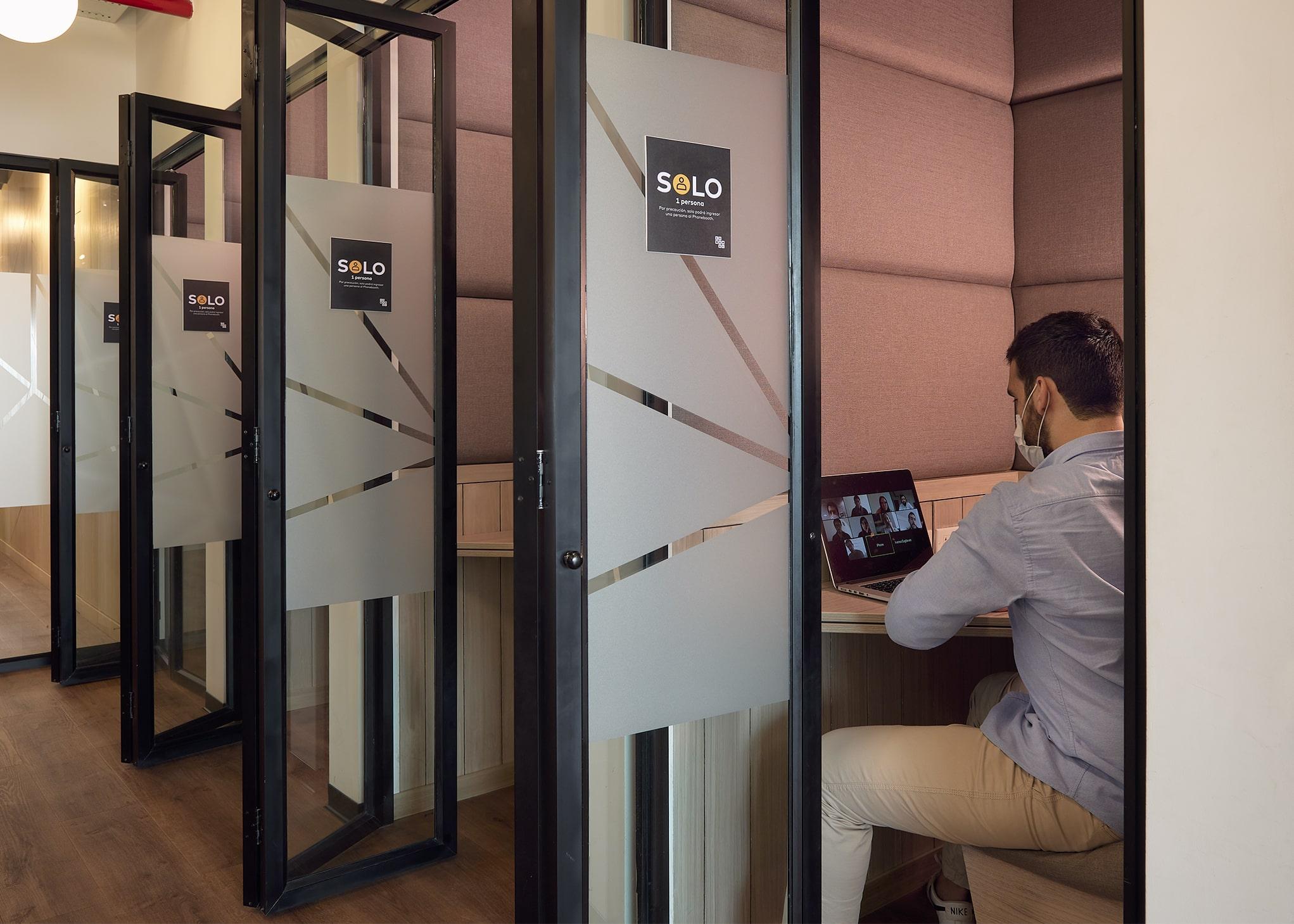 hombre teniendo una videollamada en una cabina de la oficina satelite