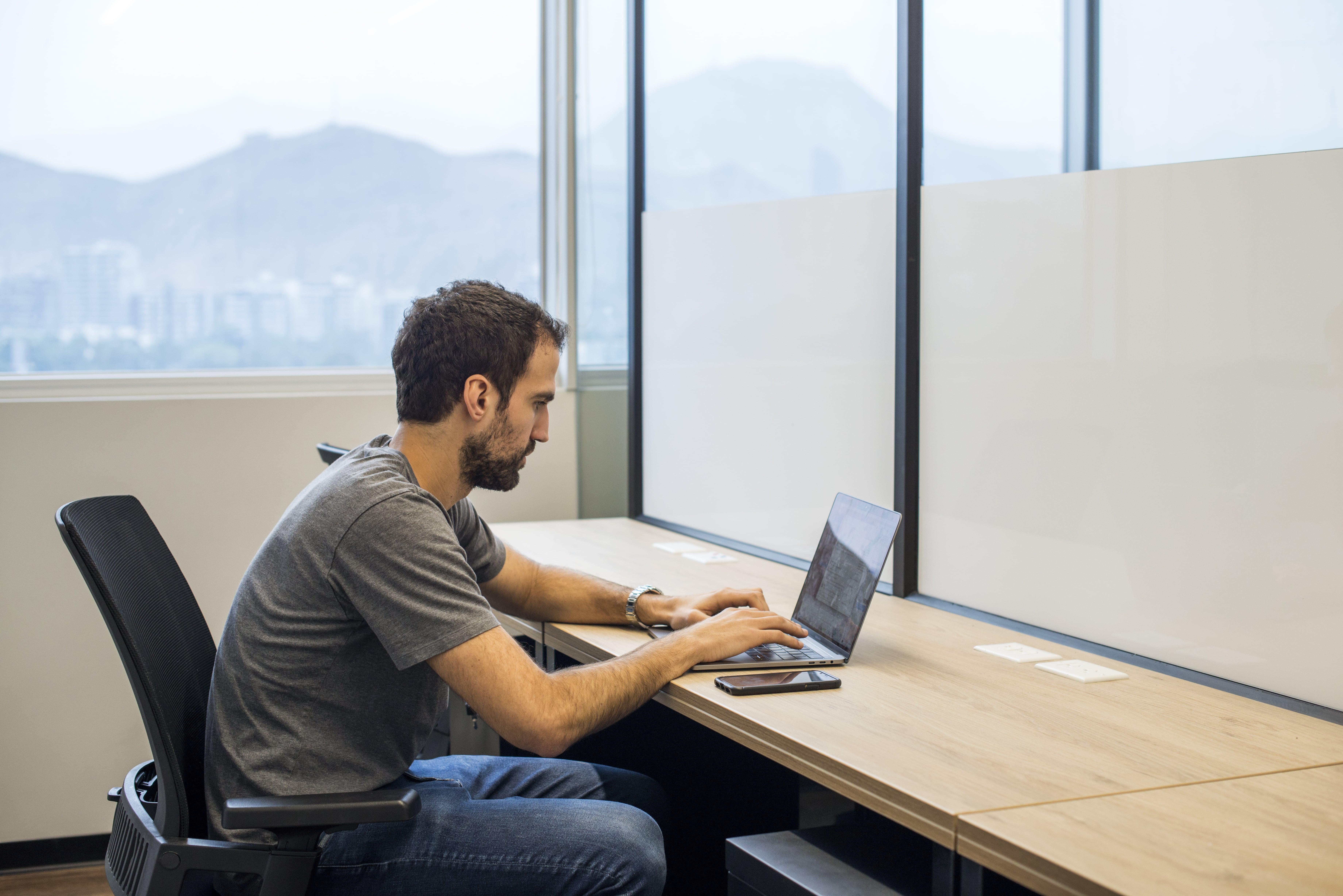 hombre trabajando con su laptop en una oficina de comunal