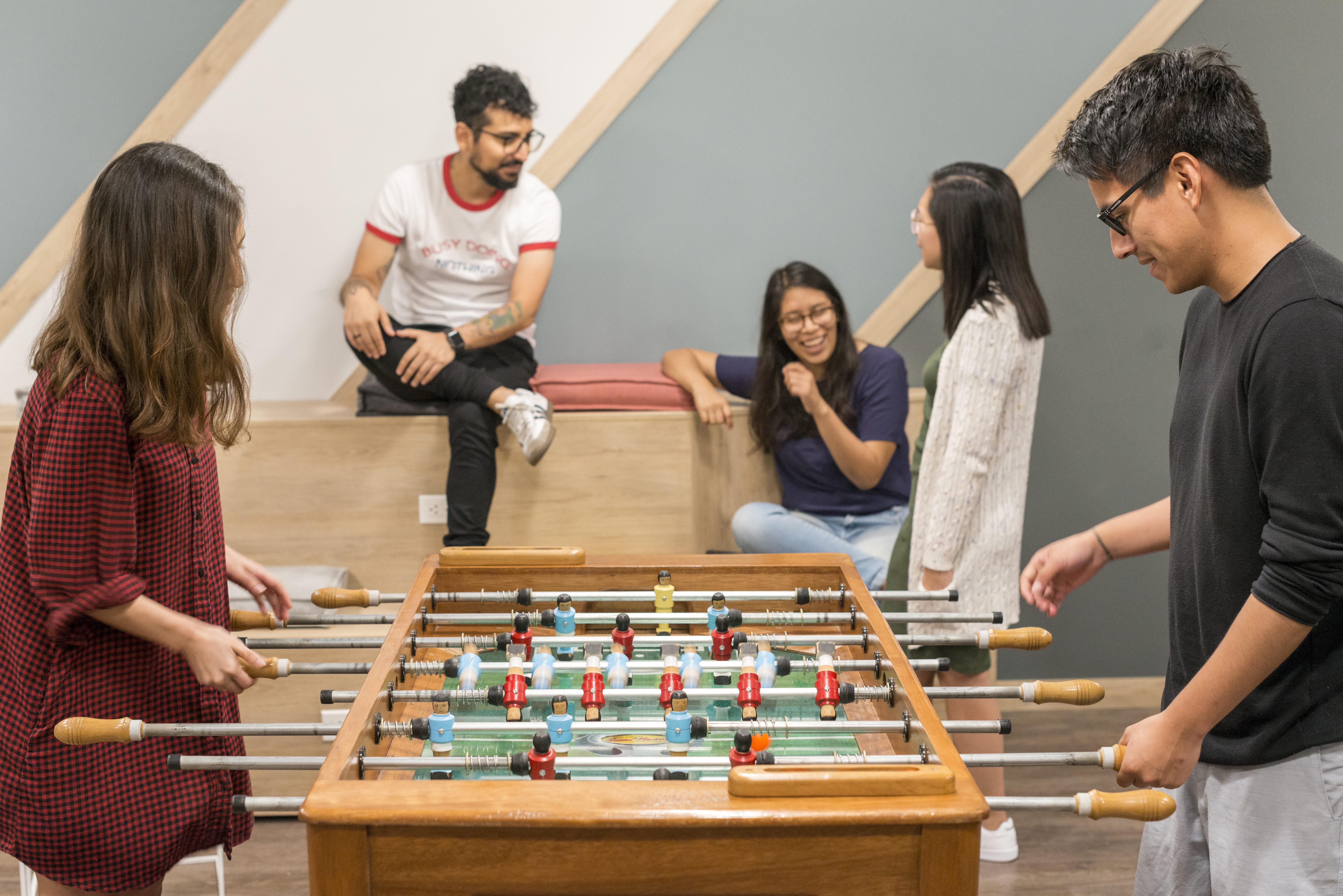 jovenes jugando futbolito de mesa en una sala de juegos de comunal