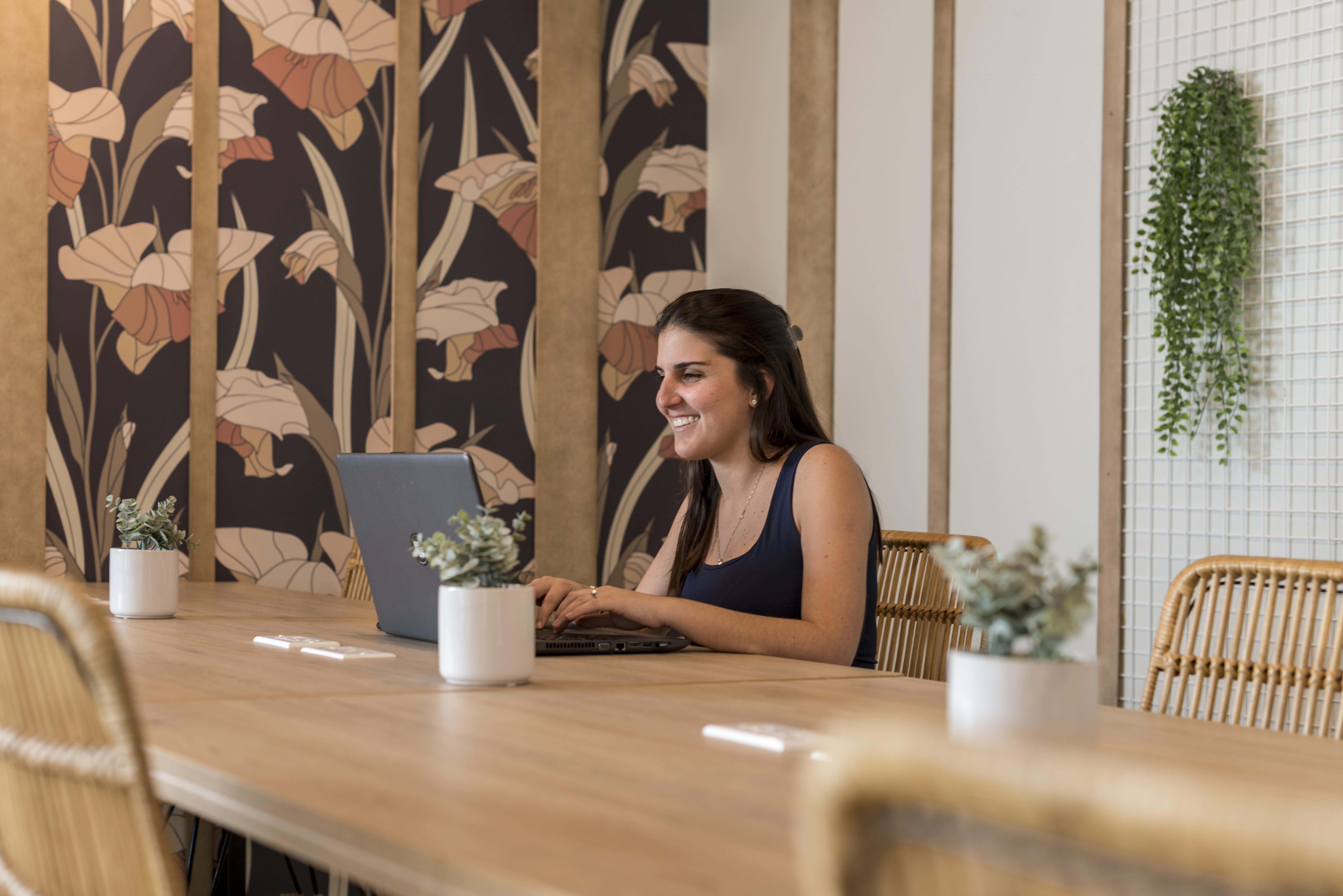 mujer con una laptop en una de las oficinas de comunal