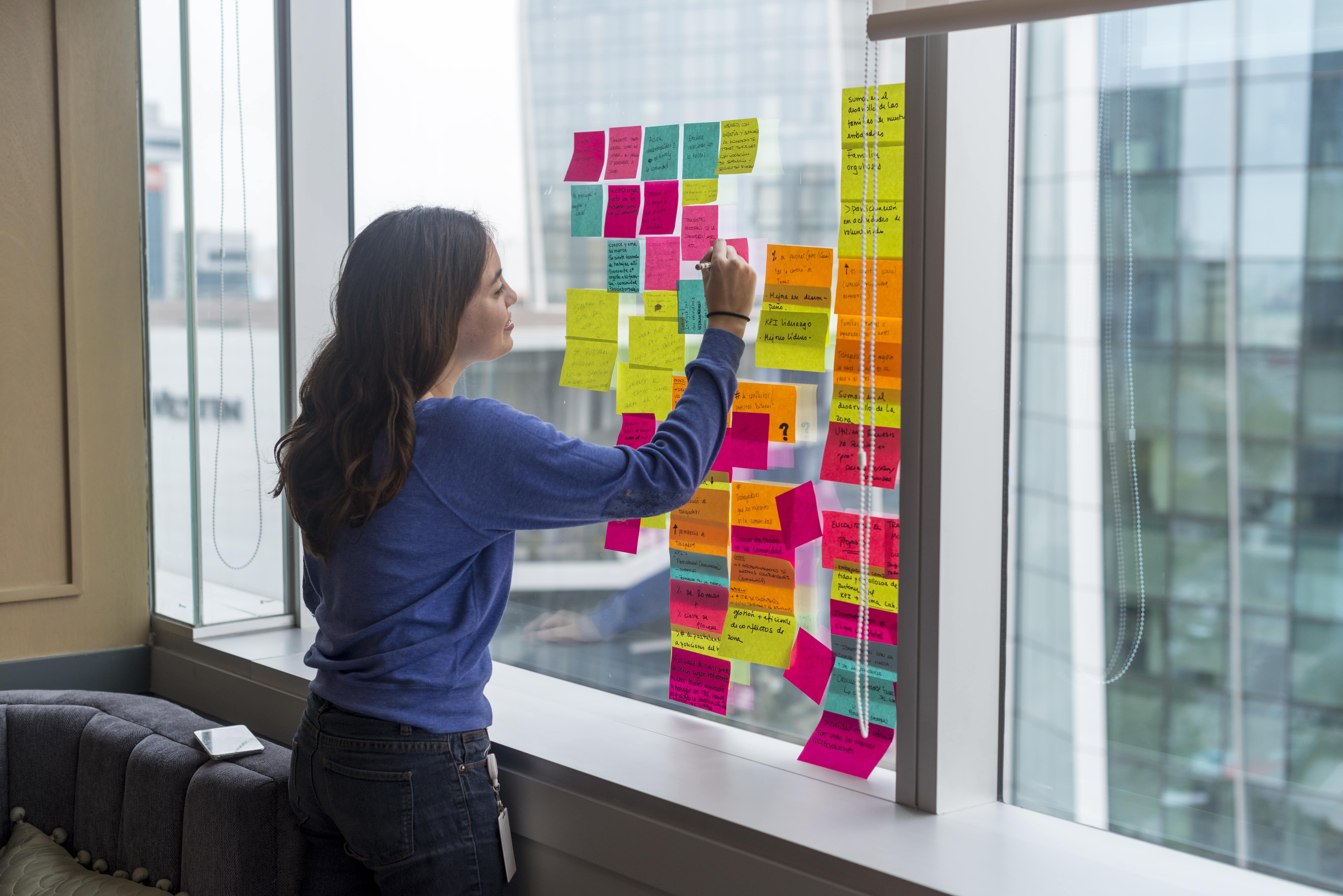 mujer haciendo brainstorming en post its
