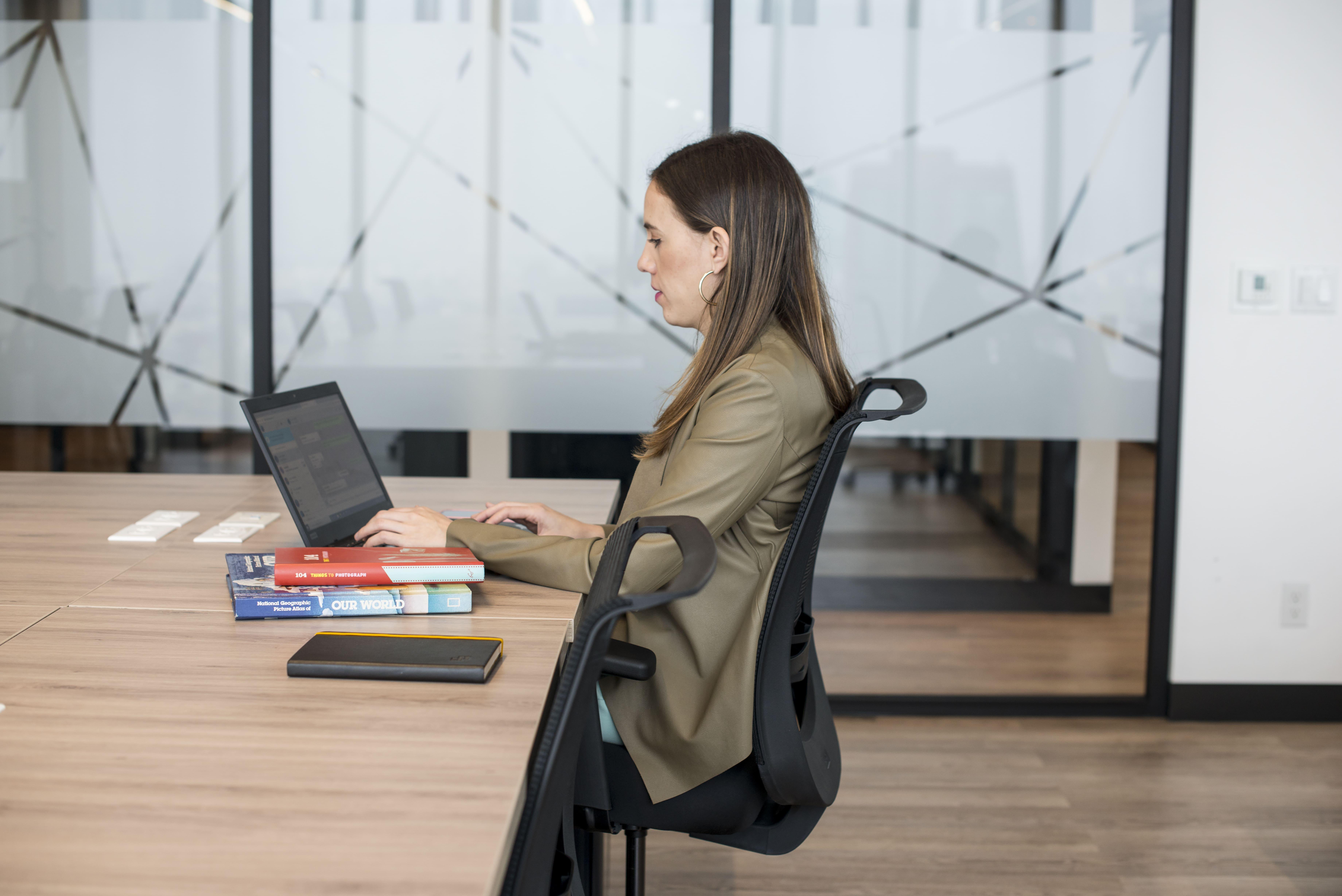 mujer joven trabajando en una silla ergonomica
