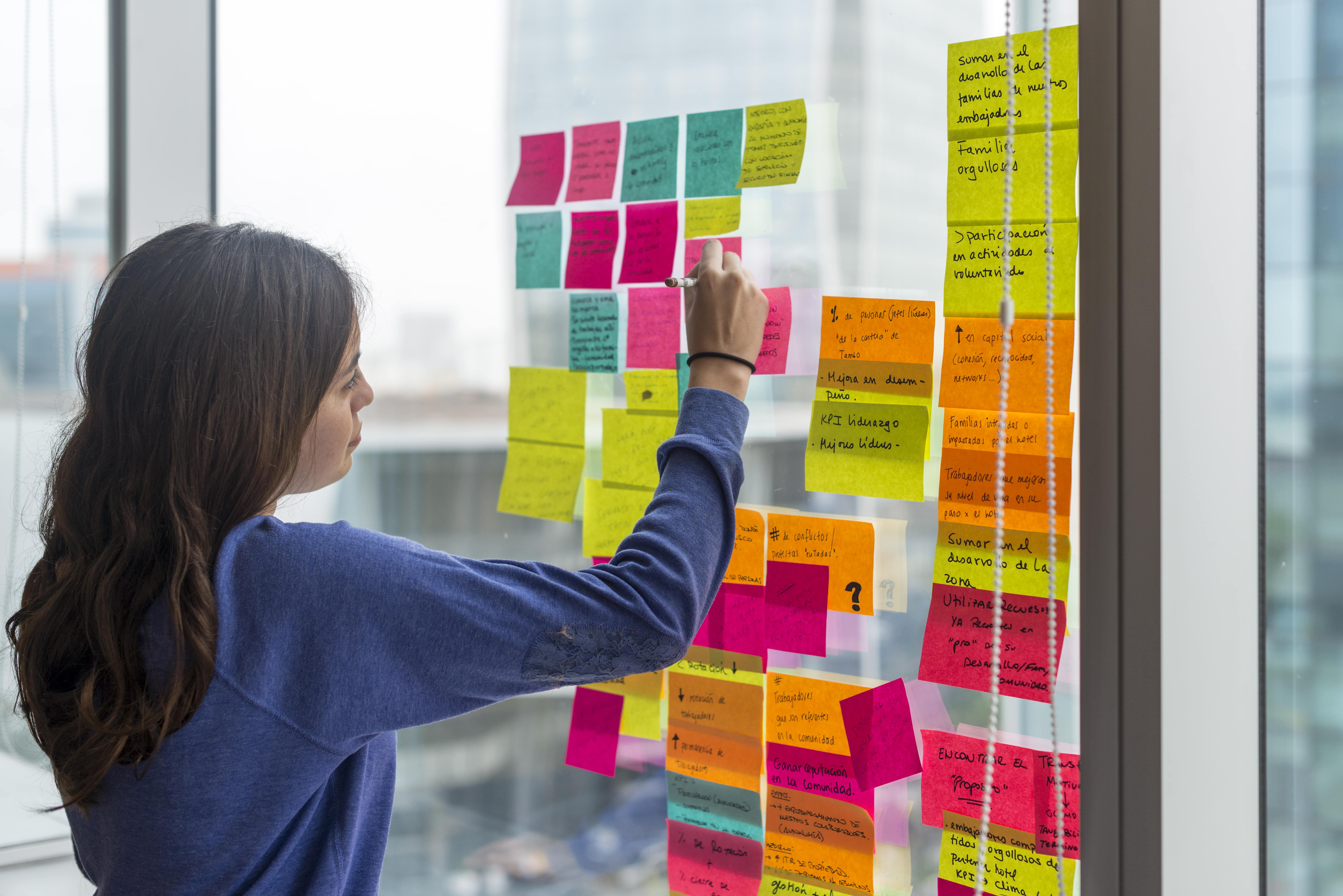 mujer pegando postits en una ventana como ejercicio de brainstorming