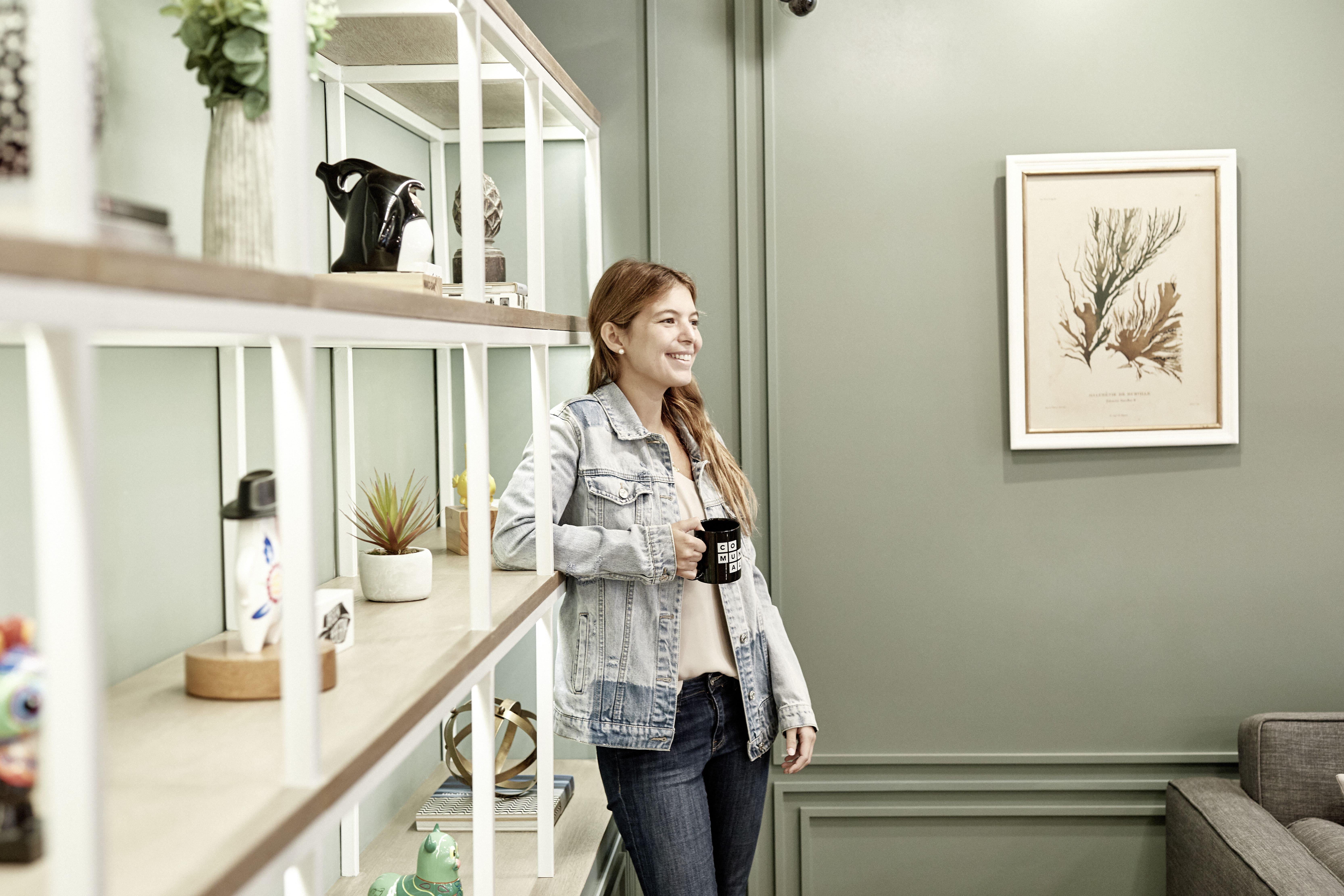 mujer sonriente tomando cafe en su casa