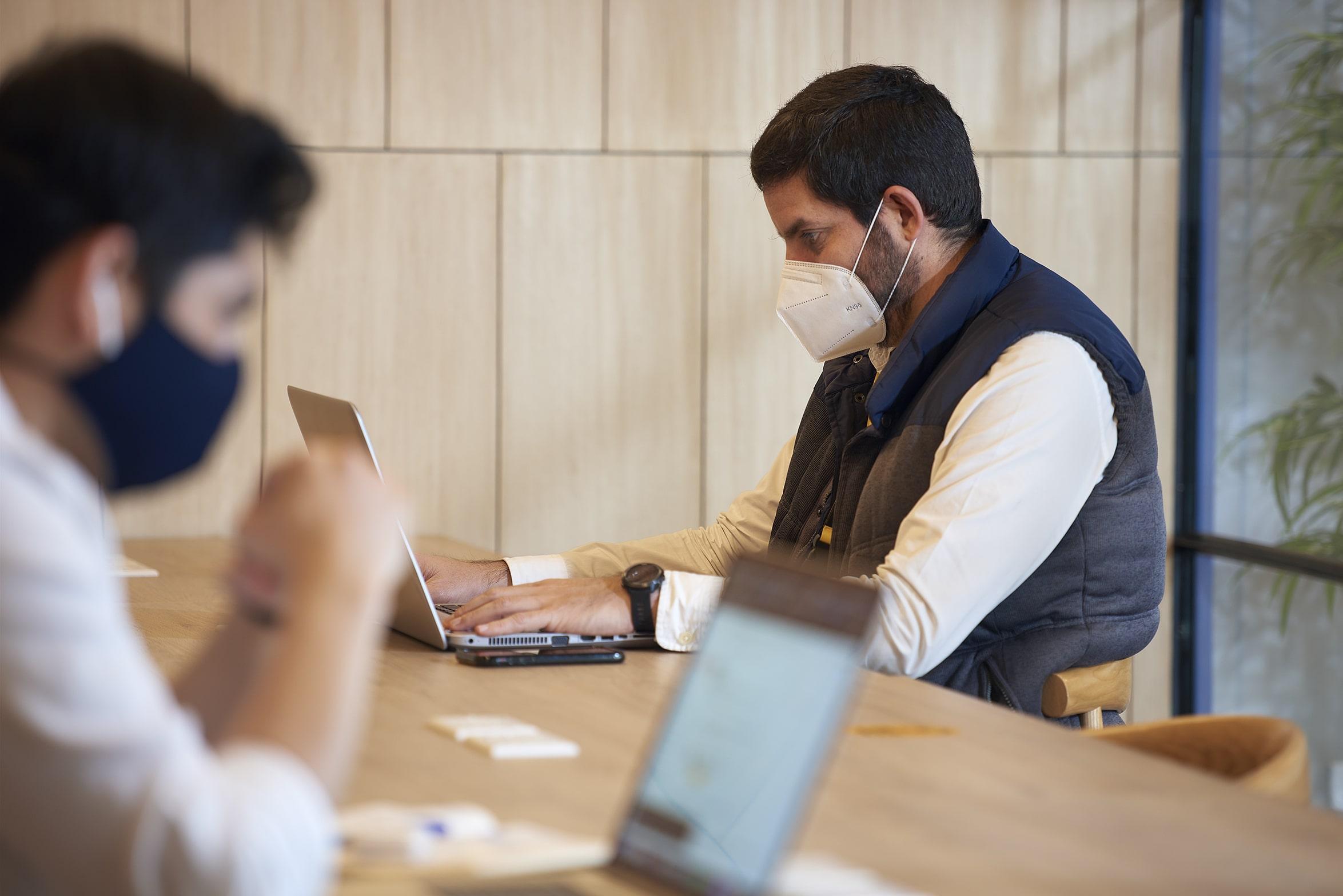 personas trabajando con mascarilla en una de las oficinas satelite